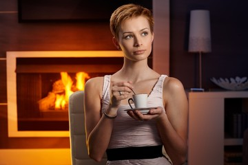 Daydreaming woman drinking coffee at home