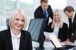 lächelnde geschäftsfrau mit ihren kollegen am arbeitsplatz