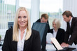 lächelnde geschäftsfrau mit ihrem team im büro