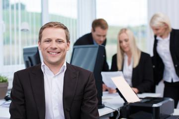 lächelnder geschäftsmann mit seinen kollegen am arbeitsplatz