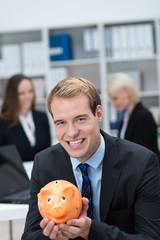 lächelnder geschäftsmann mit sparschwein
