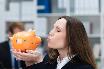 glückliche frau im büro küsst ihr sparschwein