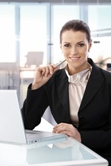 Businesswoman sitting at desk working laptop
