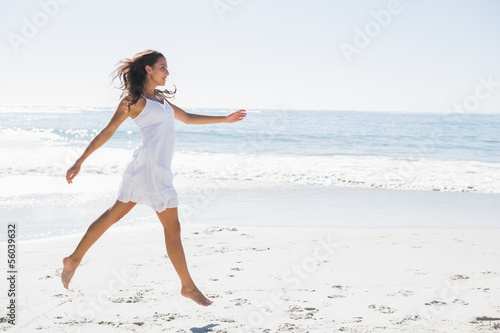 Happy brunette in white sun dress skipping on the sand