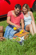 Happy couple sitting on the grass having picnic together