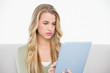 Focused pretty blonde using her tablet sitting on cosy sofa