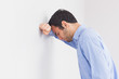 Upset man leaning his head against a wall