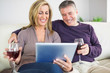 Happy couple watching their tablet pc and drinking wine