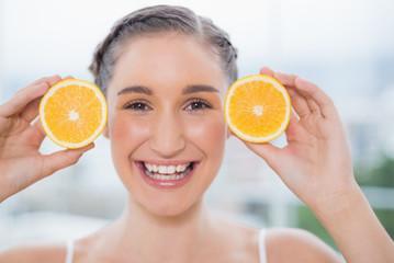 Smiling healthy brunette holding orange slices