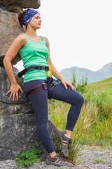 Attractive female rock climber leaning on rock face