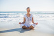 Peaceful pretty woman in lotus position on the beach