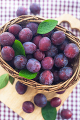 Fresh wet purple plums in a basket