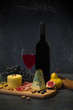 Still life with wine, cheese,ham and fruits