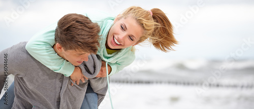 Couple embracing and having fun wearing warm clothes outside on