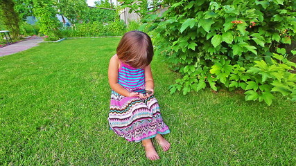 Little girl play with cat in green garden