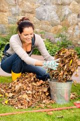 Happy woman putting dry leaves bucket yard