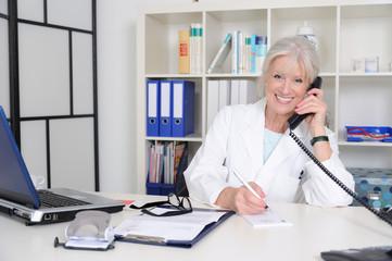 Senior Ärztin berät am Telefon..