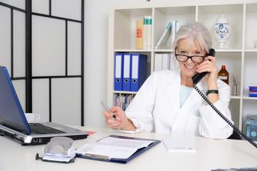 Senior Ärztin telefoniert.
