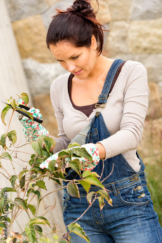 Young woman pruning tree bush autumn garden