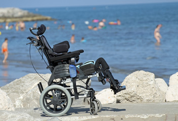 wheelchair for disabled people on the Jetty of rocks by the sea