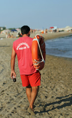 Lifeguard on the beach with a glass of soda and orange lifesaver