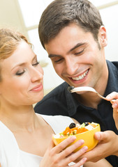 Cheerful young couple with vegetarian salad at home