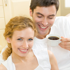 Cheerful couple with cup of coffee, indoor