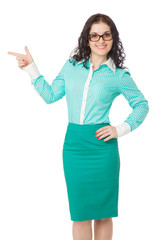 smiling slim brunette girl in green skirt and blouse pointing as