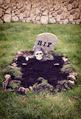 Skull with hands reaching from the grave