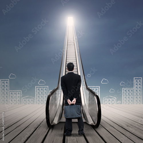 Businessman at escalator with city drawing