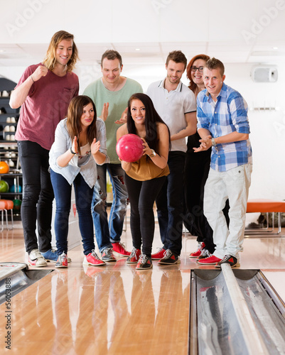 Woman Bowling While Friends Cheering