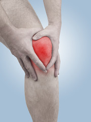 Acute pain in a man  knee. Male holding hand to spot of knee-ach