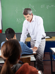 Teacher Assisting Teenage Schoolboy At Desk