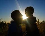Silhouette father and son at sunset