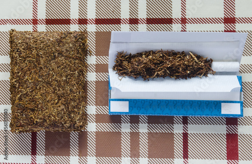 tobacco and rolling equipment on check background