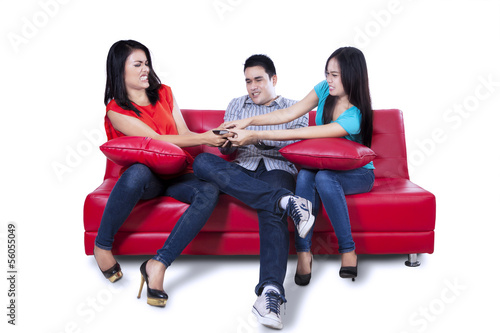 Three young teenagers fighting for remote control