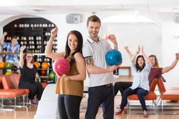 Excited Man And Woman With Bowling Balls in Club