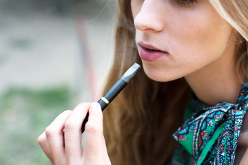 Woman smoking electronic cigarette outdoor