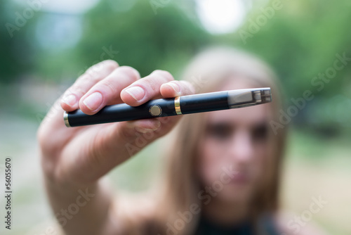 Woman holding electronic cigarette outdoor
