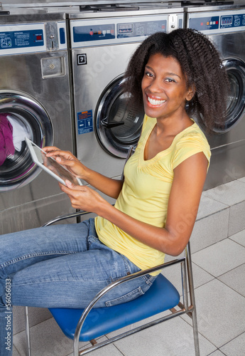 Young Woman With Digital Tablet In Laundry