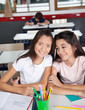 Schoolgirl Sitting With Classmate At Desk In Classroom