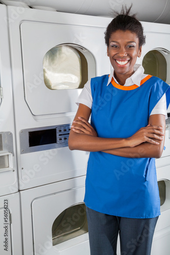 Confident Female Helper Standing In Front Of Dryers
