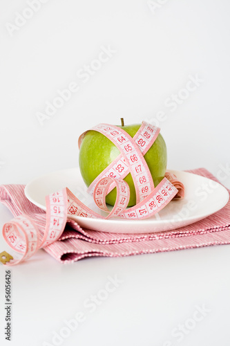 Green apple and measuring tape on a white plate