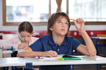 Boy Looking Up While Studying In Classroom