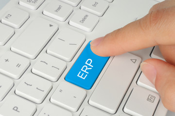 Hand pushing blue ERP button on white keyboard background .
