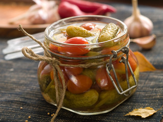 Preserved cucumber and tomato in glass jar, selective focus
