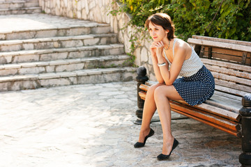 Portrait of Young Woman Sitting on the Bench