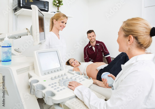 Gynecologists And Expectant Couple In Clinic