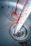 Bloody knife in kitchen sink