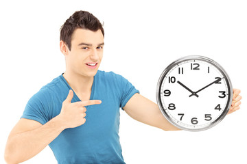 Young smiling male pointing with his hand on a wall clock